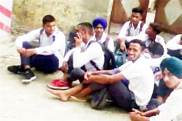 students sitting on dharna before school against teacher