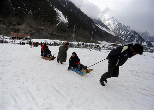 tourists enjoying snow rides in jammu and kashmir